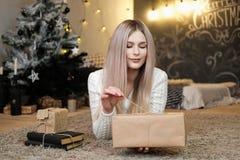 Das blonde Mädchen liegt zu Hause auf dem Teppich und hält eine Geschenkbox in ihren Händen Weihnachtsgirlanden und -häuslicher K stockfotografie