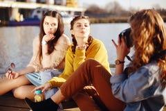Das blonde Mädchen macht Fotos ihrer brunette Freundinnen auf der alten Kamera Sie senden ihre Küsse, Lächeln, Lachen Mädchen mit stockbild