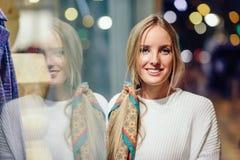Das blonde Mädchen, das mit defocused städtischer Stadt lächelt, beleuchtet nachts Lizenzfreie Stockbilder
