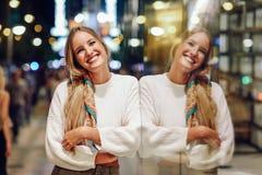 Das blonde Mädchen, das mit defocused städtischer Stadt lächelt, beleuchtet nachts Stockbilder