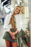 Das blonde Mädchen, das mit defocused städtischer Stadt lächelt, beleuchtet nachts Lizenzfreies Stockfoto