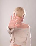 Das blonde Mädchen mit dem kurzen Haar, das eine Hand im Protest lokalisiert hält Stockfoto