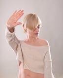 Das blonde Mädchen mit dem kurzen Haar, das eine Hand im Protest lokalisiert hält Stockfotografie