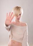 Das blonde Mädchen mit dem kurzen Haar, das eine Hand im Protest lokalisiert hält Lizenzfreie Stockfotografie
