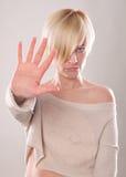 Das blonde Mädchen mit dem kurzen Haar, das eine Hand im Protest lokalisiert hält Stockbilder