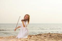 Das blonde Mädchen mit einer Violine im Freien Stockbild