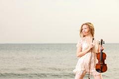 Das blonde Mädchen mit einer Violine im Freien Stockfotos