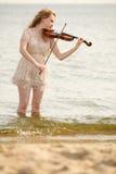 Das blonde Mädchen mit einer Violine im Freien Stockfotografie