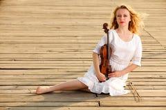 Das blonde Mädchen mit einer Violine im Freien Stockfoto