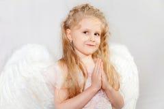 Das blonde Mädchen mit Flügeln eines Engels Lizenzfreie Stockfotografie