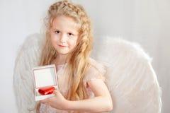 Das blonde Mädchen mit Flügeln eines Engels und der Valentinstagkarte Stockfotografie
