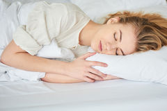Das blonde Mädchen schläft auf weißem Bett Stockbild