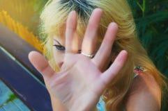 Das blonde Mädchen schließt eine Hand, die ein Gesicht zu es nie entfernt worden war anschlag stockbild