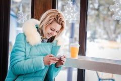 Das blonde Sitzen des Mädchens in einem Café Stockfotografie