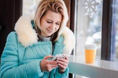 Das blonde Sitzen des Mädchens in einem Café Lizenzfreie Stockbilder