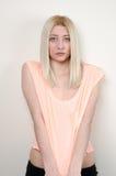 Das blonde woma, das auf weißer Wand sich lehnt, tragen eine Erntespitze und kurze Hosen Lizenzfreies Stockfoto