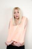Das blonde woma, das auf weißer Wand sich lehnt, tragen eine Erntespitze und kurze Hosen Lizenzfreies Stockbild