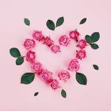 Das Blumenherz, das von der Rosarose gemacht wird, blüht und Grün verlässt auf Draufsicht des Pastellhintergrundes Flaches Lagean Lizenzfreie Stockfotografie