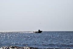 Das Boot hetzt durch das Meer In den Bootsflüchtlingen Meerblick am Abend Schattenbild eines Motorboots und der Leute in ihm gege Lizenzfreie Stockfotos