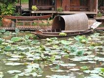 Das Boot mit einem Paddel ist neben dem Lotosteich lizenzfreies stockbild