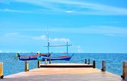 Das Boot mit zwei Fischern hat Holzbrücke im Meer mit blauer Himmel backg Stockfotografie