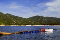 Das Boot am Pier auf dem Hintergrund von Bergen und von Strand Lizenzfreies Stockfoto