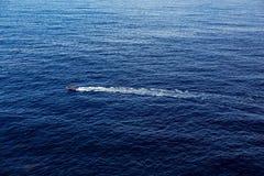 Das Boot schwimmt auf das Wasser und hinterlässt eine Spur Stockbilder