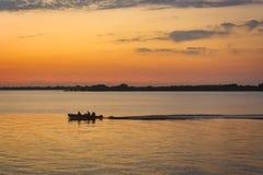 Das Boot segelt auf ruhiges Wasser bei Sonnenuntergang lizenzfreie stockfotografie