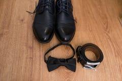 Das Bräutigam ` s Hochzeitszubehör Schwarzer Ledergürtel, schwarze Krawatte und schwarze Schuhe auf einem hölzernen Hintergrund Stockbilder