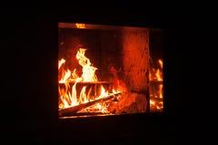 Das Brüllen flammt in einem modernen Kamin mit der glänzenden Schiefergestaltung stockfoto