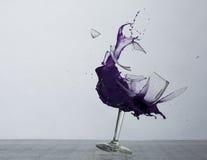 Das Brechen des Weinglases mit purpurroter Flüssigkeit Lizenzfreie Stockbilder