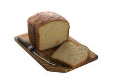 Das Brot wird auf ein Schneidebrett geschnitten Lizenzfreie Stockbilder