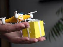 Das Brummen nah oben von quadrocopter mit dem Paket müde stockfoto