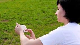 Das Brunette Mädchen, das auf dem grünen Gras im Park sitzt und benutzt den Smartphone Eine junge Frau sendet Mitteilungen in Soz stock footage