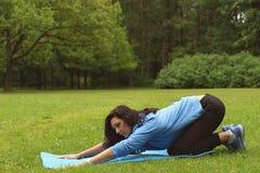 Das Brunettemädchen nimmt an Yoga im Sommerpark teil lizenzfreie stockbilder