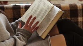 Das Buch ist auf dem Schoss eines Mädchens stock video