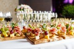 Das Buffet an der Aufnahme Gläser Wein und Champagner Zusammenstellung von Canapes auf hölzernem Brett Bankettservice lizenzfreies stockbild
