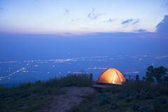 Das Campingzelt auf dem Hügel und den Ansichten der Stadt Lizenzfreie Stockfotografie