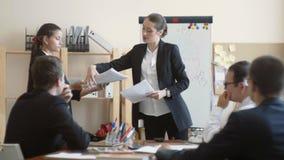 Das Chefmädchen hebt wichtige Papiere auf und liest sie mit einem bedrohlichen Blick stock video