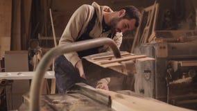 Das craftman arbeitet an elektrischer Sägemaschine Sägen einer großen hölzernen Stange Staub und Chips zerstreuen stock footage
