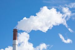 Das dämpfende Rohr der Anlage oder der Fabrik auf dem Hintergrund des blauen Himmels Lizenzfreies Stockfoto