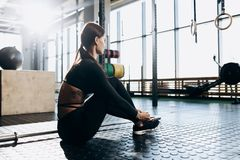 Das dünne dunkelhaarige Mädchen, das in der schwarzen Sportkleidung gekleidet wird, sitzt auf dem Boden in der Turnhalle stockbilder