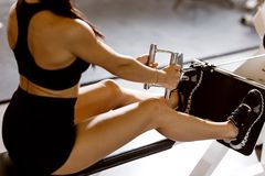 Das dünne dunkelhaarige Mädchen, das in der schwarzer Sportspitze und -kurzen Hosen gekleidet wird, arbeitet auf der Übungsmaschi stockfoto