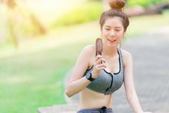 Das dünne Mädchen des gesunden Sports, das jugendlich ist, entspannen sich, SchokoladenEiscreme essend lizenzfreies stockbild
