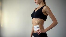 Das dünne Mädchen, das Magersuchtanmerkung, kranke Frau hält, benötigt Hilfe, Bulimie, Abführung stockfotos