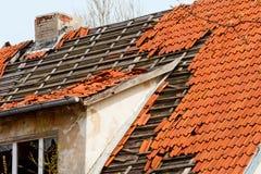 Das Dach des alten Hauses mit einer schädigenden Beschichtung von roten Keramikfliesen Stockbilder