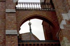 Das Dach und die Haube des historischen Gebäudes sind durch einen Ziegelsteinbogen sichtbar lizenzfreie stockfotos