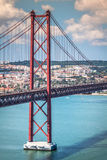 Das 25 De Abril Bridge ist eine Brücke, welche die Stadt von Lissabon anschließt Stockfotografie