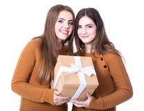 Días de fiesta y amistad - muchachas con la caja de regalo aislada en blanco Imagenes de archivo