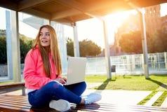 Ð-¡, das den weiblichen Jugendlichen sitzt auf Parkbank mit offenem Laptop am sonnigen Tag des Frühlinges, Aufflackernsonne schäd Lizenzfreie Stockfotografie